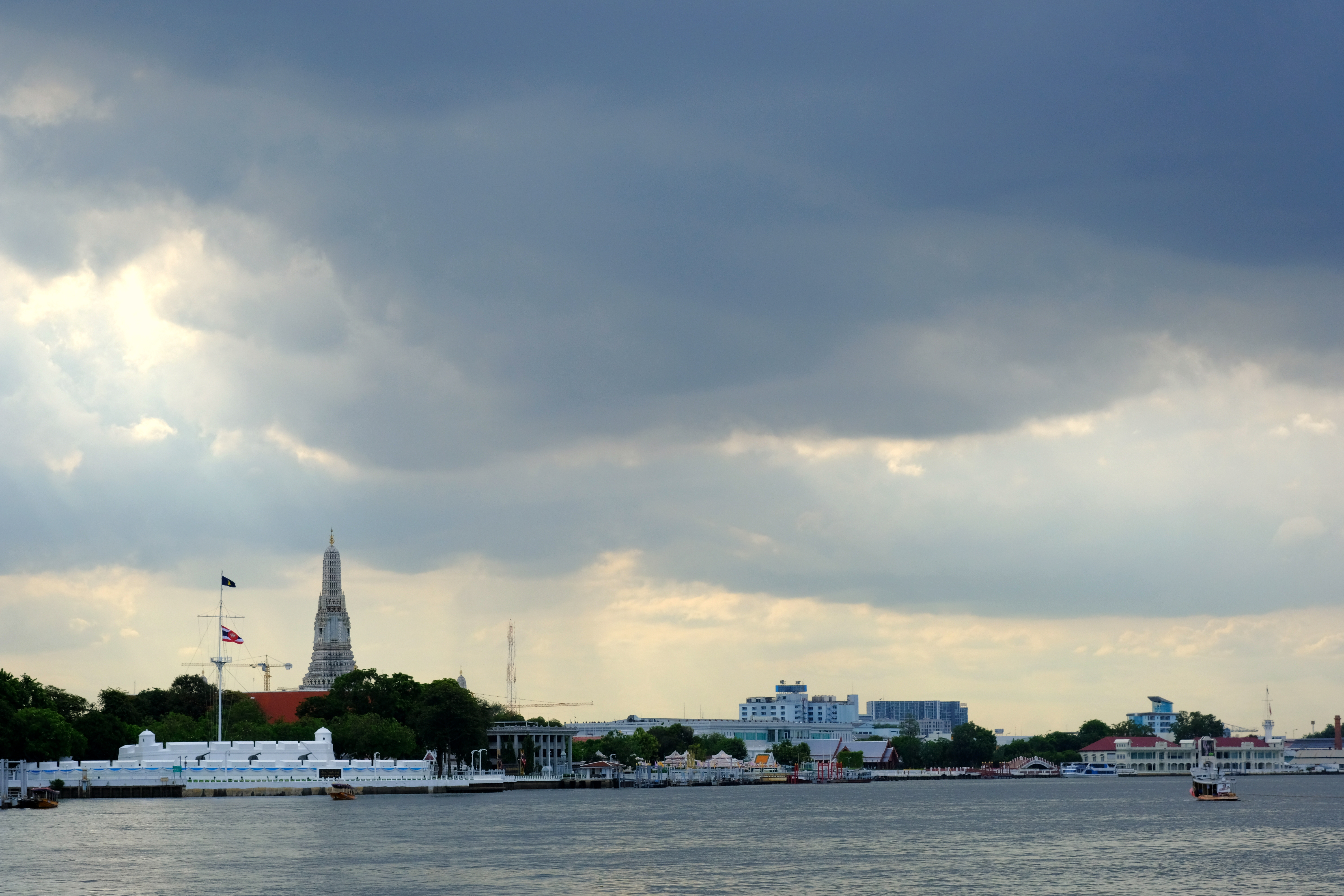 An August sky over the Chao Phraya river with Wat Arun in the distance.